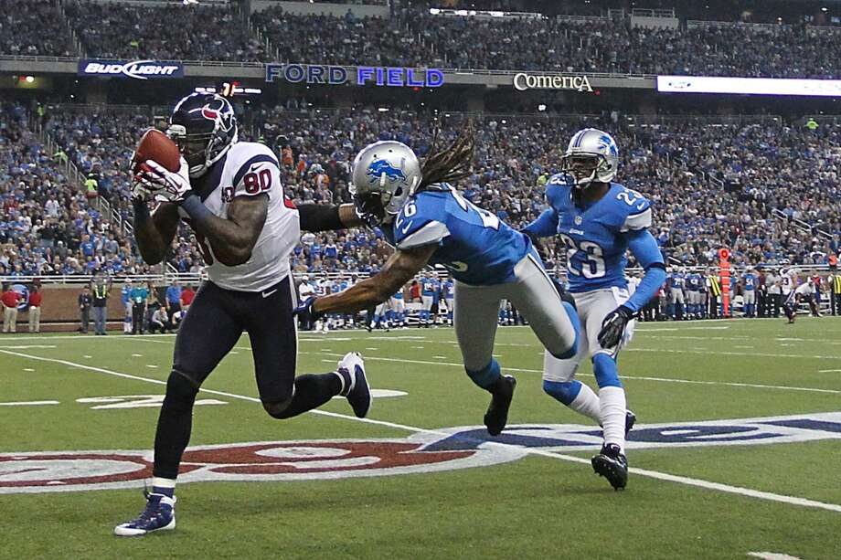 Texans wide receiver Andre Johnson (80) makes a catch on a long pass against Lions free safety Louis Delmas (26) and  cornerback Chris Houston (23) during the second quarter. (Karen Warren / Houston Chronicle)