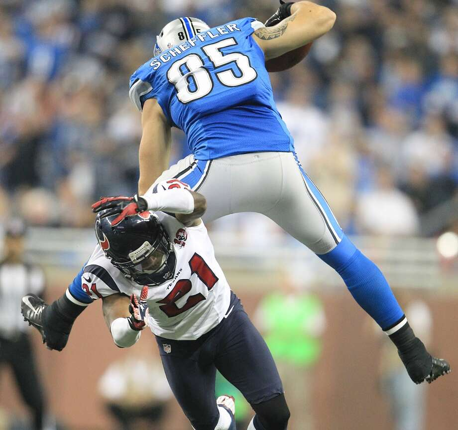 Lions tight end Tony Scheffler (85) jumps over Texans defensive back Brice McCain (21) during overtime. (Karen Warren / Houston Chronicle)
