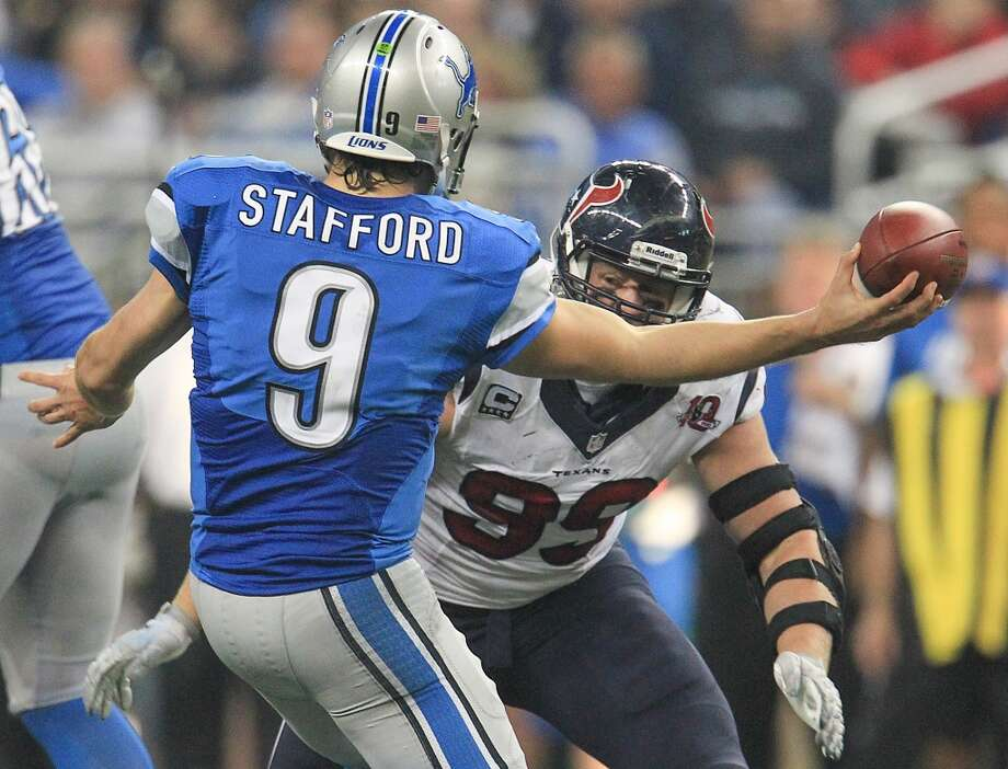 Lions quarterback Matthew Stafford (9) tries to get a pass off as he is hit by Texans defensive end J.J. Watt (99) during the fourth quarter. (Karen Warren / Houston Chronicle)