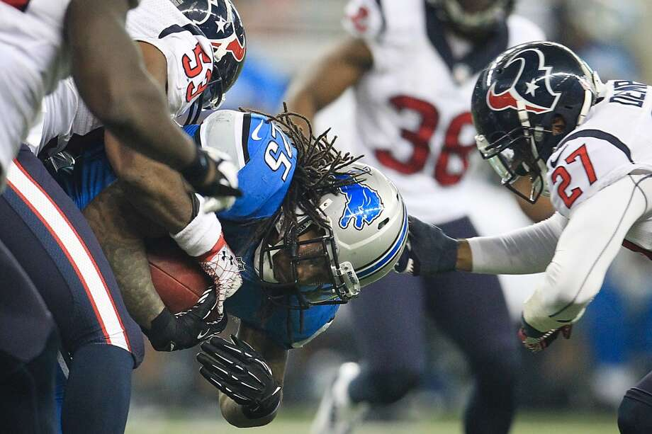 Lions running back Mikel Leshoure (25) is wrapped up by the Texans defense. (Karen Warren / Houston Chronicle)