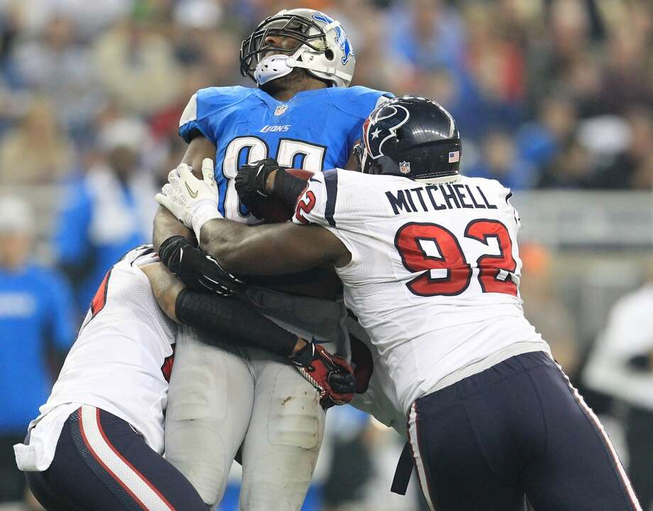 Lions tight end Brandon Pettigrew (87) gets hit hard by Texans nose tackle Earl Mitchell (92) during the third quarter. (Karen Warren / Houston Chronicle)