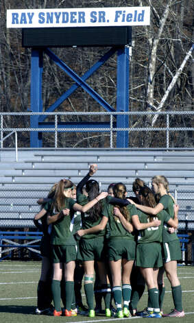 The Green Wave bonds during a pre-match huddle before New Milford High School girls' soccer's state class 'LL' semifinal match vs. Newtown in Waterbury. Nov. 17, 2012 Photo: Norm Cummings