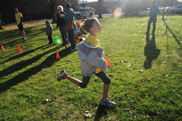 Zoe Harris, 10, races toward the finish to complete a 7 minute mile in the kids race as the Greenwich Alliance for Education hosts its second Turkey Trot at Roger Sherman Baldwin Park in Greenwich, Conn., Nov. 24, 2012. Threads and Treads ran the event which raised money for Greenwich public school educational programs. Photo: Keelin Daly / Stamford Advocate Riverbend Stamford, CT