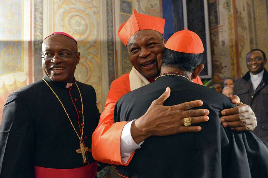 Nigerian cardinal John Onaiyekan (C) greets visitors druing the courtesy visit after being appointed by the pontif on November 24, 2012 at the Apostolico palace at the Vatican. Six non-European prelates are set to join the Catholic Church's College of Cardinals, a move welcomed by critics concerned that the body which will elect the future pope is too Eurocentric. Photo: VINCENZO PINTO, AFP/Getty Images / AFP