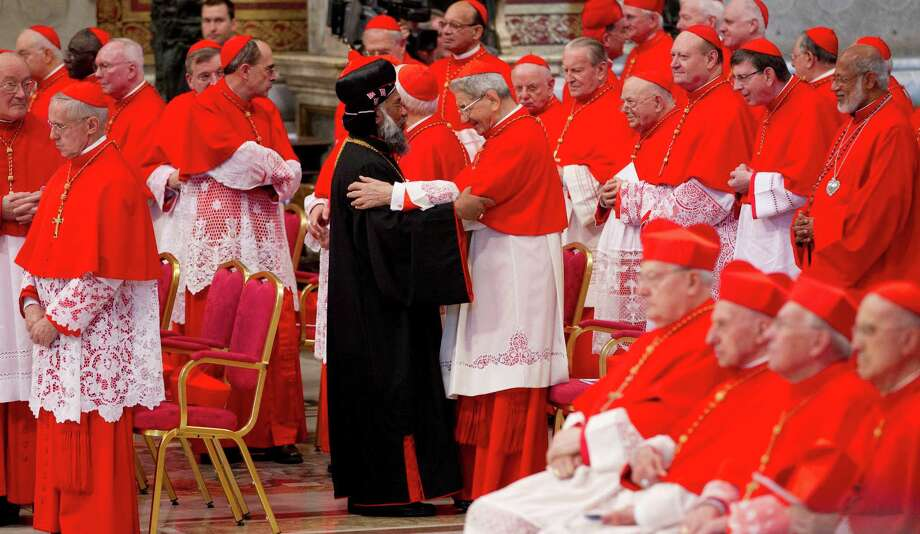 Newly elected Cardinal Baselios Cleemis Thottunkal of India, at center wearing a black suit, is greeted by cardinals during a consistory inside the St. Peter's Basilica at the Vatican, Saturday, Nov. 24, 2012. Six new cardinals are joining the elite club of churchmen who will elect the next pope, bringing a more geographically diverse mix into the European-dominated College of Cardinals. Photo: Andrew Medichini, Associated Press / AP