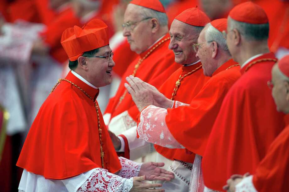 Newly elected Cardinal Luis Antonio Tagle, Archbishop of Manila, Philippines, left, is greeted by cardinals after receiving the red three-cornered biretta hat by Pope Benedict XVI  during a consistory in St. Peter's Basilica at the Vatican, Saturday, Nov. 24, 2012. Photo: Andrew Medichini, Associated Press / AP