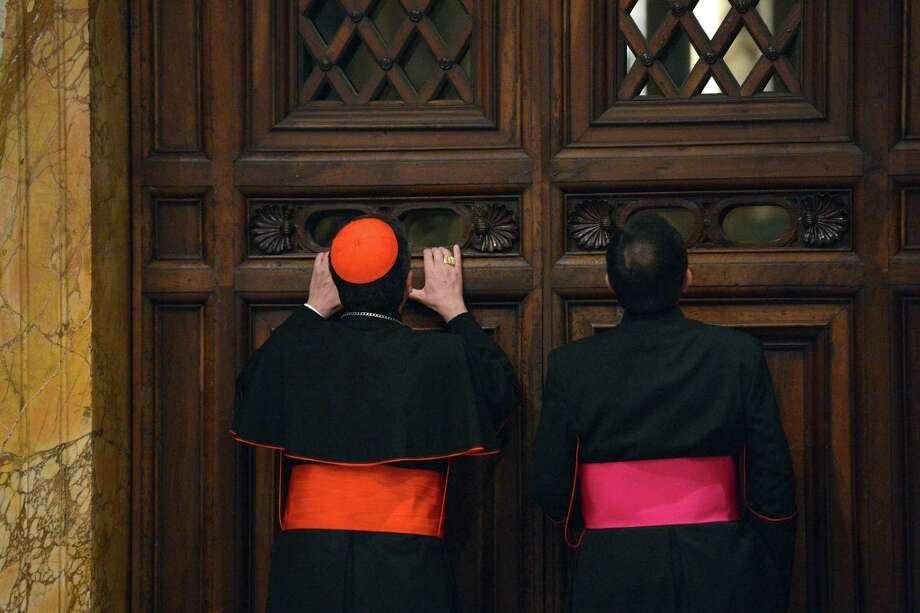Italian cardinal Giuseppe Betori (L) and a bishop take a glimpse through a door during the courtesy visit to the cardinals on November 24, 2012 at the Apostolico palace at the Vatican. Photo: VINCENZO PINTO, AFP/Getty Images / AFP