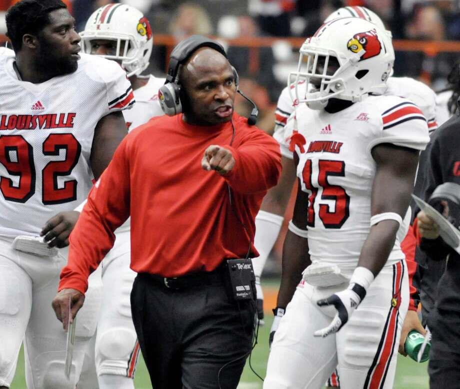 Louisville head coach Charlie Strong gives Andrew Johnson (15) a lecture at the end of the first quarter against Syracuse during an NCAA college football game in Syracuse, N.Y., Saturday, Nov. 10, 2012. (AP Photo/Kevin Rivoli) Photo: KEVIN RIVOLI, Associated Press / FR60349 AP