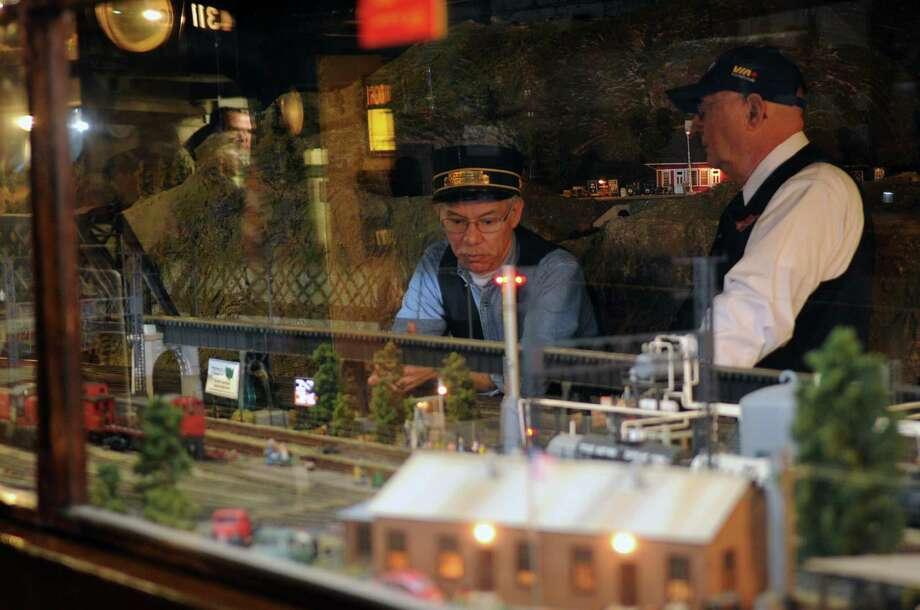 Club members Mike Ribuffo, left, and Bob Blonski, right, stand inside an enormous railroad scene which is on display for the Stamford Model Railroad Club's 73rd annual holiday open house at St. John Episcopal's Church. The exhibit will be open to the public again on December 1 from 1-5 p.m. and 7-9 p.m. There is a five dollar entrance fee for adults, four dollars for children and children under 5 years old are admitted for free. Photo: Lindsay Niegelberg / Stamford Advocate