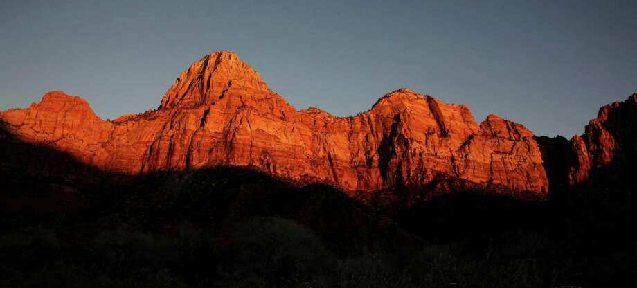 FILE - This Jan. 20, 2011 file photo shows shadows creeping up on sandstone cliffs glowing red as the sun sets on Zion National Park near Springdale, Utah. This is one of a number of scenic attractions, parks and other sites near enough to Las Vegas to add to itineraries as a day trip when visiting the gambling capital. (AP Photo/Julie Jacobson, file) Photo: Julie Jacobson, STF / AP