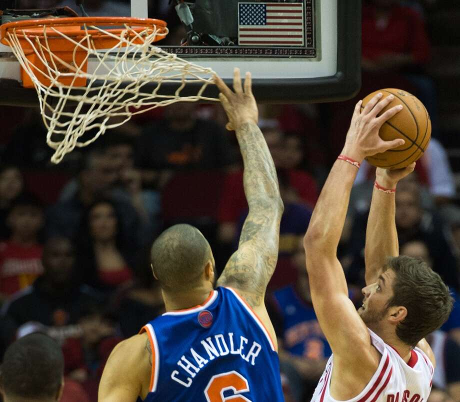 Rockets forward Chandler Parsons (25) goes to the basket as Knicks center Tyson Chandler (6) gets tangled in the net.  Parsons had a career-high 31 points. (Smiley N. Pool / Houston Chronicle)