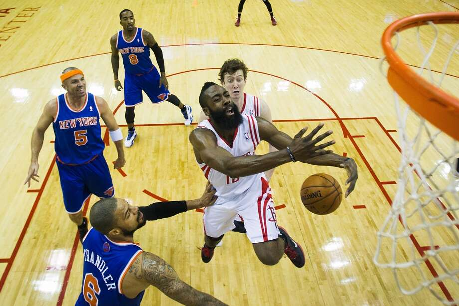 Rockets guard James Harden (13) loses the ball as he tries to drive past Knicks center Tyson Chandler (6). (Smiley N. Pool / Houston Chronicle)