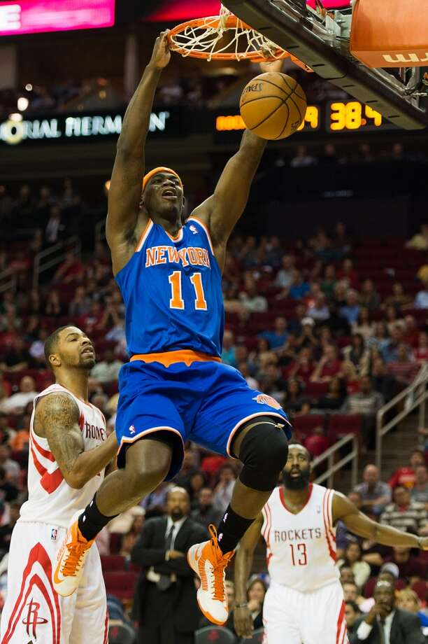 Knicks forward Ronnie Brewer (11) dunks the ball as Rockets power forward Marcus Morris (2) and shooting guard James Harden (13) look on. (Smiley N. Pool / Houston Chronicle)