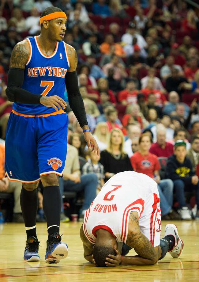 Rockets power forward Marcus Morris (2) collapses to the floor after being hit by an errant elbow as Knicks small forward Carmelo Anthony (7) looks. (Smiley N. Pool / Houston Chronicle)