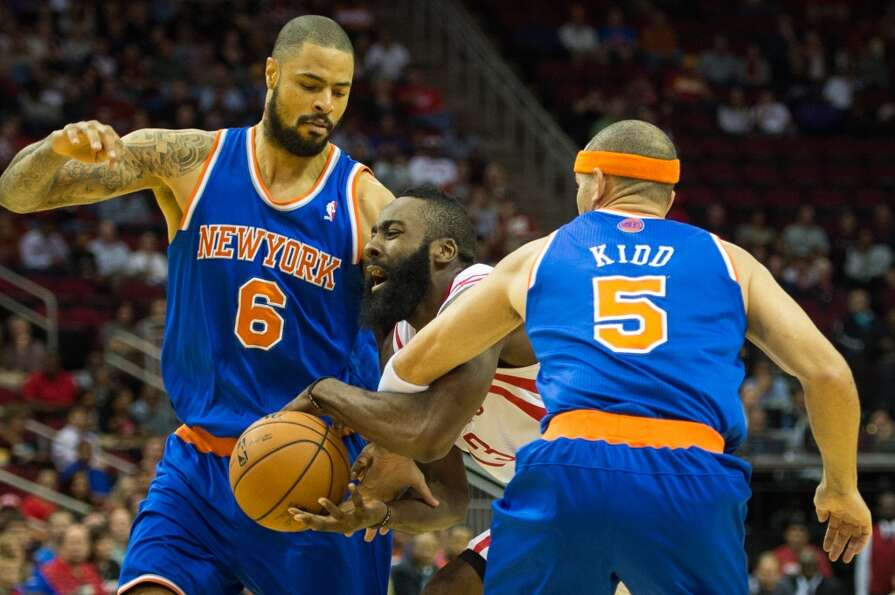 Rockets guard James Harden (13) drives between Knicks point guard Jason Kidd (5) and center Tyson Ch