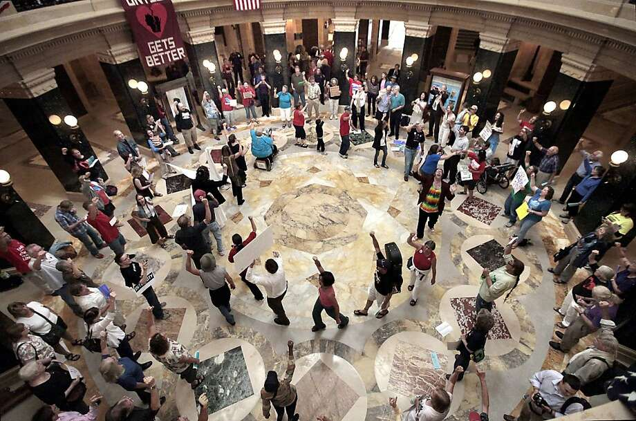 In this Sept. 7, 2012 photo, dozens of singers gather in the state Capitol rotunda for the 455th consecutive Solidarity sing along in the wake of a crackdown on protests without a permit by new Capitol Police Chief David Erwin. Most of the demonstrations against Wisconsin Gov. Scott Walker ended a long time ago. But every weekday at noon, a few dozen people still gather inside the state Capitol and sing protest songs for an hour. (AP Photo/Wisconsin State Journal, John Hart) Photo: John Hart, Associated Press