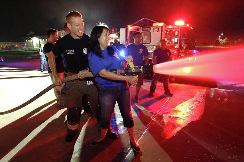 Firefighter Cody Davenport supports Citizen's Fire Academy student Annamarie Ramos as she tries her hand at managing a fire hose. Ramos is among a group of 19 people from the department's first Citizen's Fire Academy. The 12-week long class met once a week and learned about how the San Antonio Fire Department works and how firefighters do their jobs. The goal of SAFD is to offer public awareness and education. During this class session, the students learned in class about how firefighters tackle a fire scene and then saw an a fire demonstration out at the academy facility. Last night's class was topped off with some of the students getting a chance at handling a fire hose.
