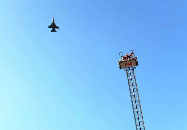 A Texas Air National Guard F-16 flies over the extended aerial platform of a SAFD truck on Tuesday, Sept. 25, 2012. The department's Citizen's Fire Academy class were given a tour of several firefighting vehicles on the grounds of the training academy. Photo: Kin Man Hui, San Antonio Express-News / ©2012 San Antonio Express-News