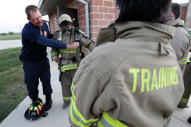 San Antonio Fire Academy instructor Ben Marberry helps student Albert Alvizo with his breathing apparatus as other members of the Citizen's Fire Academy try on bunker gear for the first time on Tuesday, Sept. 25, 2012. The group put on protective fire suits, learned how a breathing apparatus works and ran a series of exercises with a fire hose. Photo: Kin Man Hui, San Antonio Express-News / ©2012 San Antonio Express-News