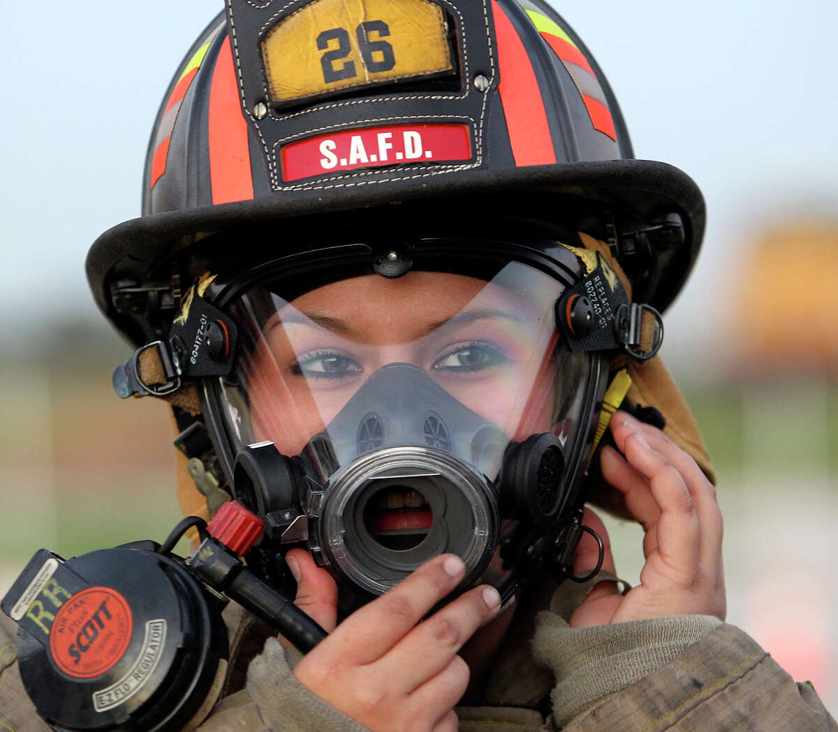 Megan Mendez puts on a mask along with her helmet and bunker gear with other students of the San Antonio Fire Department's Citizen's Fire Academy on Tuesday, Sept. 25, 2012. The group put on protective suits, learned how to use a breathing apparatus and ran a series of exercises with a fire hose.
