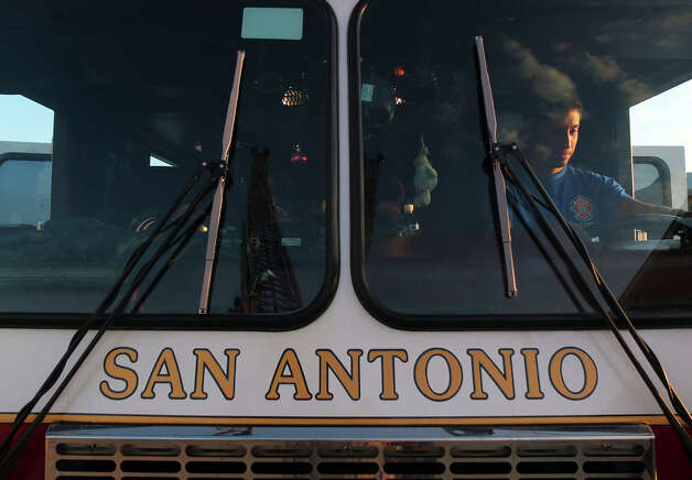 Albert Alvizo sits the driver's seat of a San Antonio Fire Department ladder truck on Tuesday, Sept. 25, 2012. Alvizo is part of the department's first Citizen's Fire Academy. The group of 19 people are given an opportunity to experience and learn about what life is like for the city's firefighters. On Tuesday, the group was given a tour of several firefighting vehicles on the grounds of the training academy. Photo: Kin Man Hui, San Antonio Express-News / ©2012 San Antonio Express-News