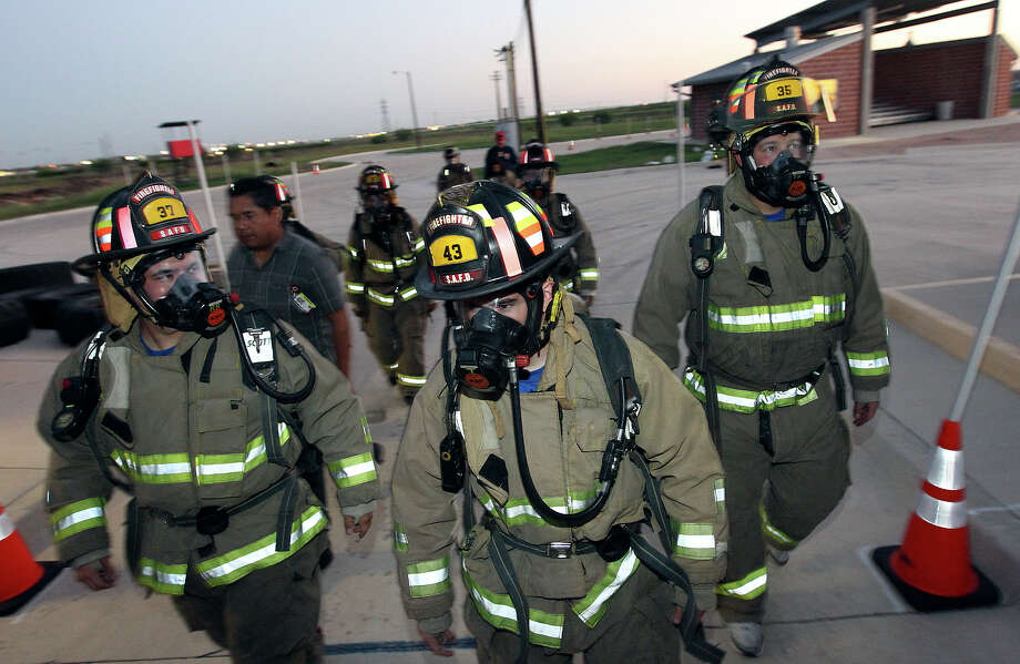 Pete Hernadez (from left), Michael Henderson and SAFD PIO Christian Bove prepare to walk up several flights of stairs in their bunker gear and breathing apparatus during Week 6 of San Antonio Fire Department's Citizen's Fire Academy on Tuesday, Sept. 25, 2012. The group put on the suits, learned how a breathing apparatus works and ran a series of exercises with a fire hose. Photo: Kin Man Hui, San Antonio Express-News / ©2012 San Antonio Express-News
