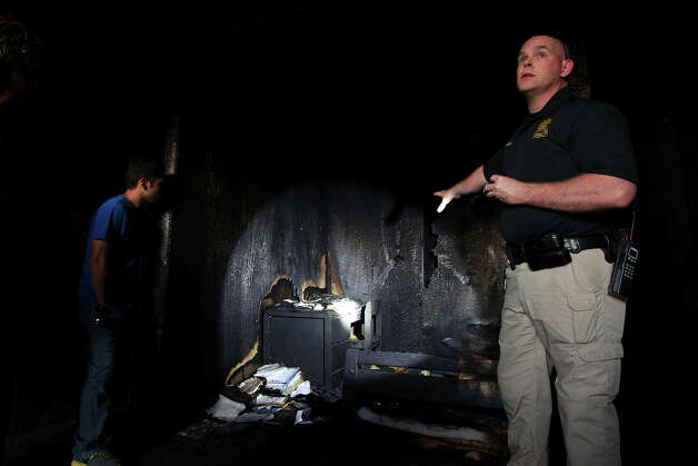 Arson Invsestigator Lt. Ken Campbell (right) explains what he looks for in fire scene as Citizen's Fire Academy student Albert Alvizo gets a closer look during class on Tuesday, Oct. 9, 2012. Photo: Kin Man Hui, San Antonio Express-News / ©2012 San Antonio Express-News