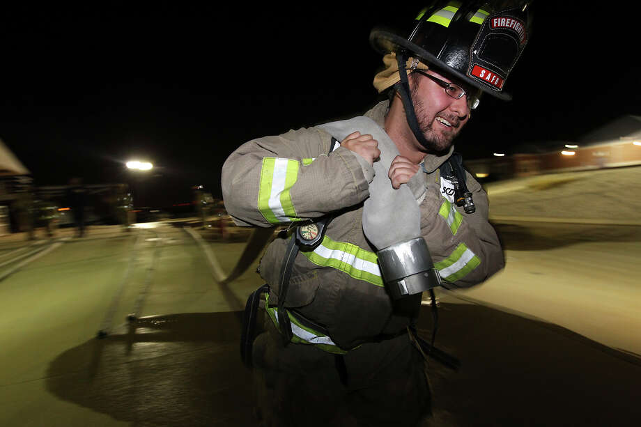 Student Chris Montemayor hauls a three-inch hose after an exercise for the San Antonio Fire Department's Citizen's Fire Academy on Tuesday, Sept. 25, 2012. Photo: Kin Man Hui, San Antonio Express-News / ©2012 San Antonio Express-News