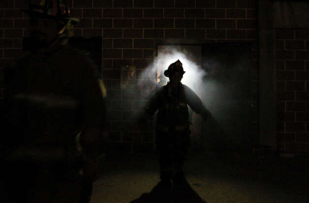A Citizen's Fire Academy students walks out from a smoke-filled building at as part of an exercise at the San Antonio Fire Academy on Tuesday, Nov. 6, 2012. About 19 students have spent one day a week for the past 12 weeks learning what firefighters experience during training and on the the job. Photo: Kin Man Hui, San Antonio Express-News / © 2012 San Antonio Express-News