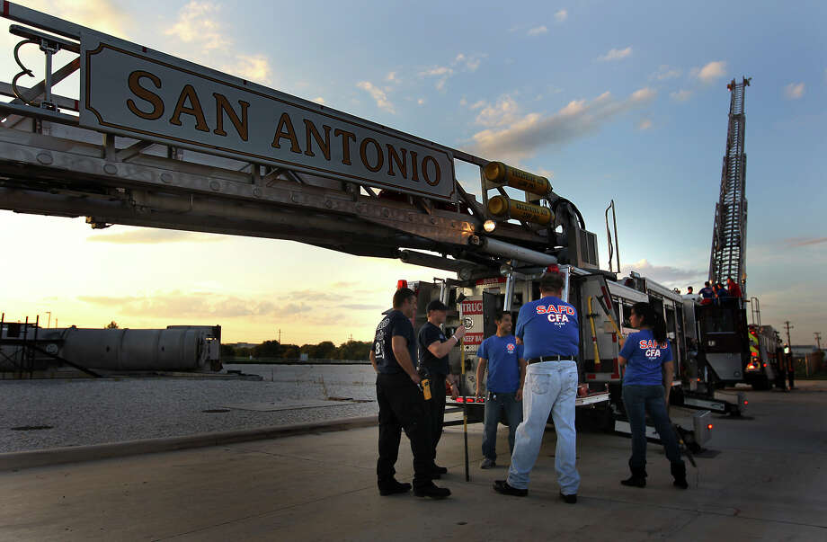 Students talk with firefighters by an aerial platform truck Week 5 of San Antonio Fire Department's Citizen's Fire Academy on Tuesday, Sept. 25, 2012. The group was given a tour of several firefighting vehicles on the grounds of the training academy. Photo: Kin Man Hui, San Antonio Express-News / ©2012 San Antonio Express-News