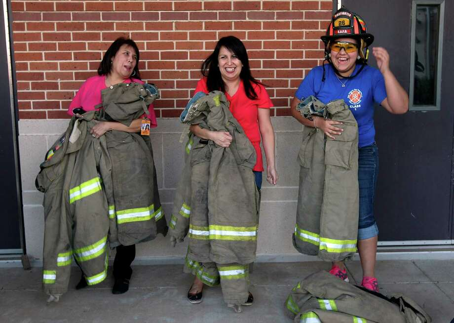 Lydia Borroel (from left), Borroel's sister Annamarie Ramos and Megan Mendez have a laugh as they put on their bunker gear or protective equipment during Week 6 of San Antonio Fire Department's Citizen's Fire Academy on Tuesday, Sept. 25, 2012. The group put on the suits, learned how a breathing apparatus works and ran a series of exercises with a fire hose. Photo: Kin Man Hui, San Antonio Express-News / ©2012 San Antonio Express-News