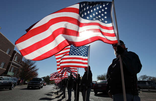 Members of the Patriot Guard Riders hold American flags outside the Cornerstone Church during the funeral service for retired Army Sgt. Joshua Michael Saturday Nov. 24, 2012 in Amarillo, Tx. Michael was one of four veterans killed when a train struck a parade float that he, his wife Daylyn Michael (not pictured) and others were riding on, Thursday Nov. 15, 2012 in Midland, Tx. Photo: Edward A. Ornelas, San Antonio Express-News / © 2012 San Antonio Express-News