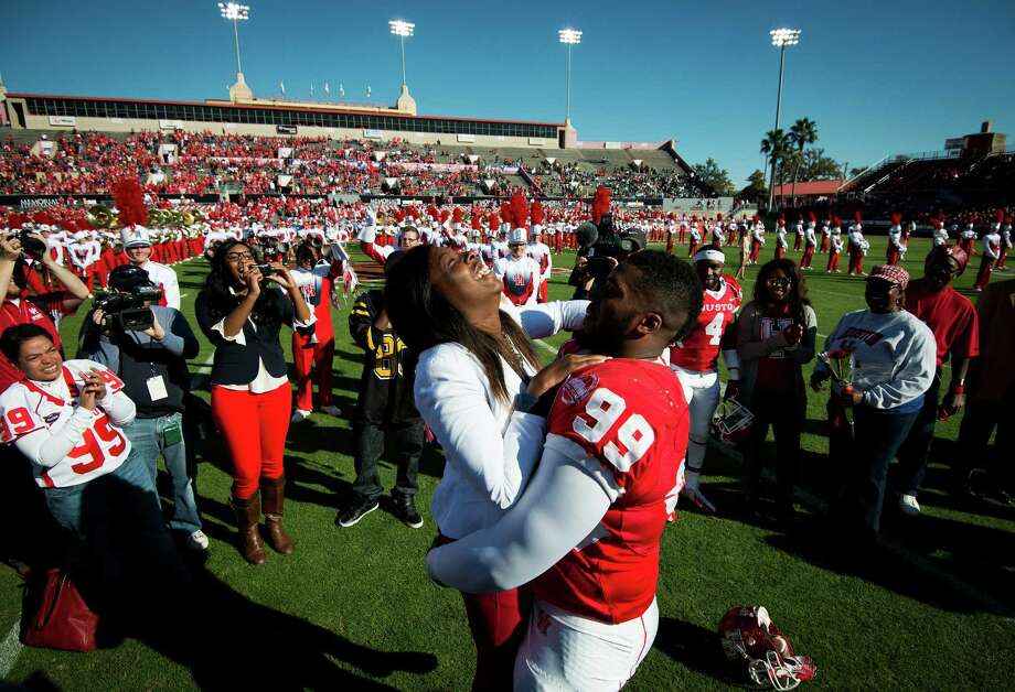 Houston defensive lineman Dominic Miller (99) lifts his girlfriend Chelsea Johnson after proposing at midfield before a college football game against Tulane at Robertson Stadium, Saturday, Nov. 24, 2012, in Houston. Johnson accepted the marriage proposal, which came during senior day festivities. Photo: Smiley N. Pool, Houston Chronicle / © 2012  Houston Chronicle