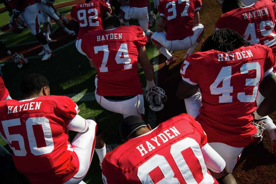 Houston players wear jerseys that all bear the name of cornerback D.J. Hayden as they kneel in prayer before a college football game against Tulane at Robertson Stadium, Saturday, Nov. 24, 2012, in Houston. Hayden had surgery to repair a tear in the main blood vessel that leads to the heart, an injury suffered when he collided with a teammate during practice earlier this month. Photo: Smiley N. Pool, Houston Chronicle / © 2012  Houston Chronicle