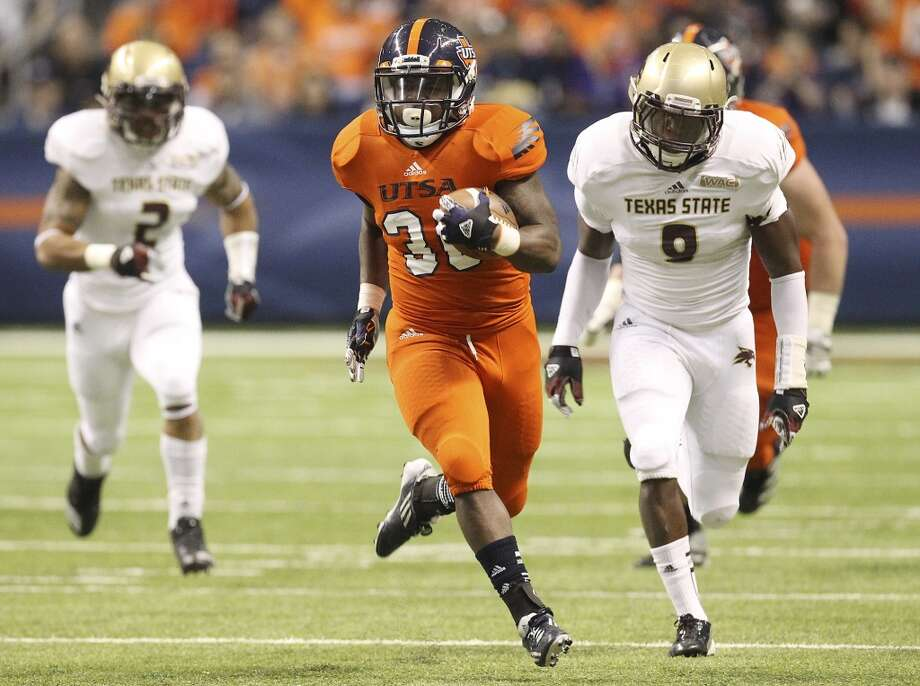 UTSA's Evans Okotcha sprints away from Texas State's Justin Iwuji (08) in the first half of their game at the Alamodome on Saturday, Nov. 24, 2012. (Kin Man Hui / San Antonio Express-News)