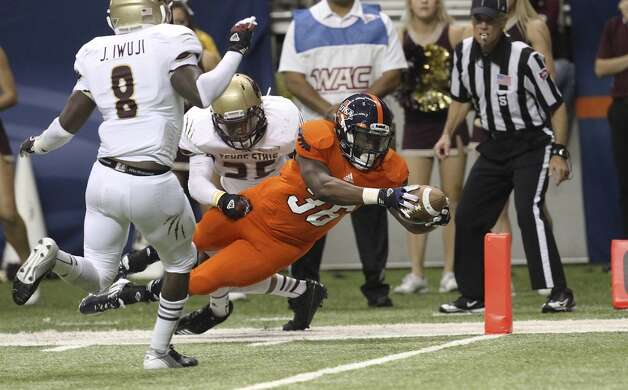 UTSA's Evans Okotcha (36) attempts to dive in for a touchdown against Texas State's Craig Mager (25) and Justin Iwuji (08) in the second half of their game at the Alamodome on Saturday, Nov. 24, 2012. Okotcha had stepped out of bounds before the attempt. The Roadrunners defeated the Bobcats 38-31. (San Antonio Express-News)
