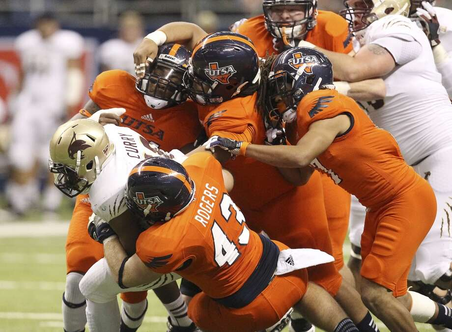 UTSA defenders pile on Texas State's Marcus Curry (28) in the first half of their game at the Alamodome on Saturday, Nov. 24, 2012. (Kin Man Hui / San Antonio Express-News)