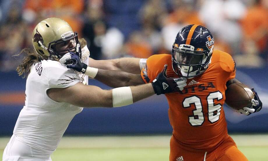 UTSA's Evans Okotcha (36) stiff arms Texas State's Jamie Clavell-Head (05) in the first half of their game at the Alamodome on Saturday, Nov. 24, 2012. (Kin Man Hui / San Antonio Express-News)