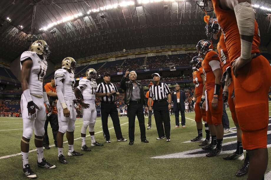 UTSA and Texas State gather for the coin toss as local businessman Ernesto Ancira throwing the coin in the air before their game at the Alamodome on Saturday, Nov. 24, 2012. (Kin Man Hui / San Antonio Express-News)