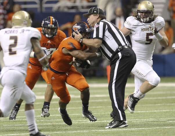 UTSA's David Glasco, II (11) collides into a game official during the game against Texas State in the second half at the Alamodome on Saturday, Nov. 24, 2012. The Roadrunners defeated the Bobcats 38-31. (Kin Man Hui / San Antonio Express-News)