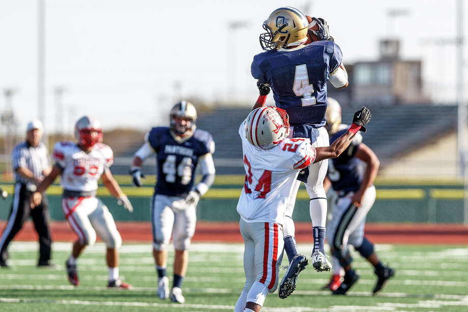 O'Connor's Nate Phillips jumps over Judson's Jaquori Brooks for a first down reception during the fourth quarter of their Class 5A Division II second round playoff game at Comalander Stadium on Nov. 24, 2012.  O'Connor won the game 34-28.  MARVIN PFEIFFER/ mpfeiffer@express-news.net Photo: MARVIN PFEIFFER, Express-News / Express-News 2012