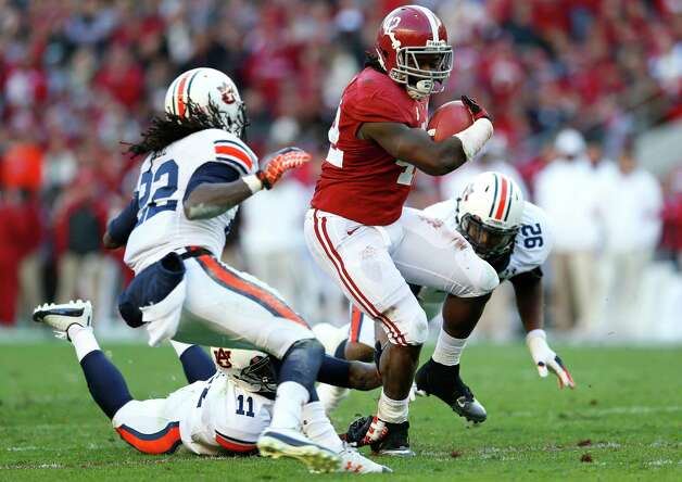 TUSCALOOSA, AL - NOVEMBER 24:  Eddie Lacy #42 of the Alabama Crimson Tide rushes against T'Sharvan Bell #22, Chris Davis #11 and Kenneth Carter #92 of the Auburn Tigers at Bryant-Denny Stadium on November 24, 2012 in Tuscaloosa, Alabama. Photo: Kevin C. Cox, Getty Images / 2012 Getty Images