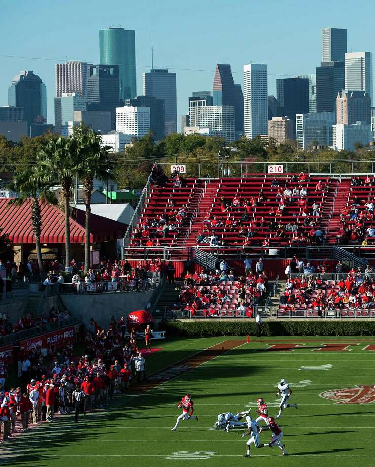 The downtown skyline looms over the stadium as Houston, in red, faces Tulane in the final game at Robertson Stadium on Saturday, Nov. 24, 2012, in Houston. The stadium, which officially opened in 1942, will be demolished and replaced with a state-of-the-art facility in time for the 2014 football season. Photo: Smiley N. Pool, Houston Chronicle / © 2012  Houston Chronicle