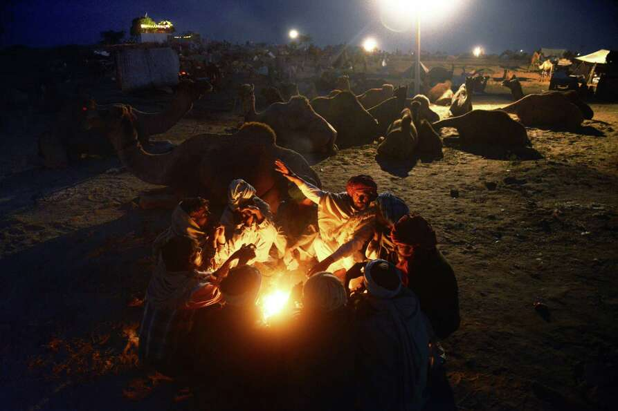 Men sit around a fire right before dawn at the camel fair grounds in the outskirts of the small town