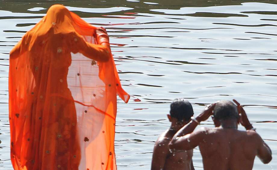 A Hindu woman bathes in the Pushkar Lake during the annual cattle fair in Pushkar, Rajasthan, India, Saturday, Nov. 24, 2012.  Pushkar, located on the banks of Pushkar Lake, is a popular Hindu pilgrimage spot that is also frequented by foreign tourists who come to the town for the annual cattle fair and camel races. Photo: Rajesh Kumar Singh, Associated Press / AP