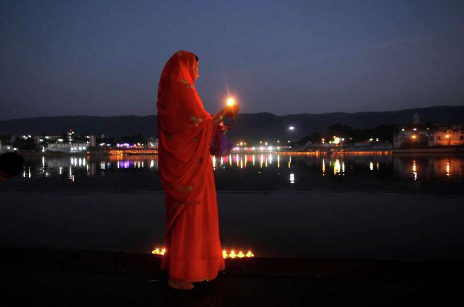 An Indian Hindu devotee holds a traditional oil lamp as she performs evening prayers near the Pushkar Lake during the annual cattle fair at Pushkar, Rajasthan, India. Pushkar, located on the banks of the Pushkar Lake, is a popular Hindu pilgrimage spot that is also frequented by foreign tourists who come to the town for the annual cattle fair and camel races. Photo: Rajesh Kumar Singh, Associated Press / AP