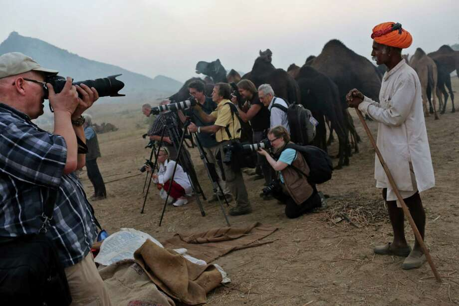Foreign tourists crowd around an Indian camel herder and camels as they take pictures at the annual Pushkar  Fair in Pushkar, Rajasthan, India, Thursday, Nov. 22, 2012.The annual camel and livestock fair attracts thousands of livestock dealers who bring thousands of camels, horses, and cattle. Photo: Kevin Frayer, Associated Press / AP