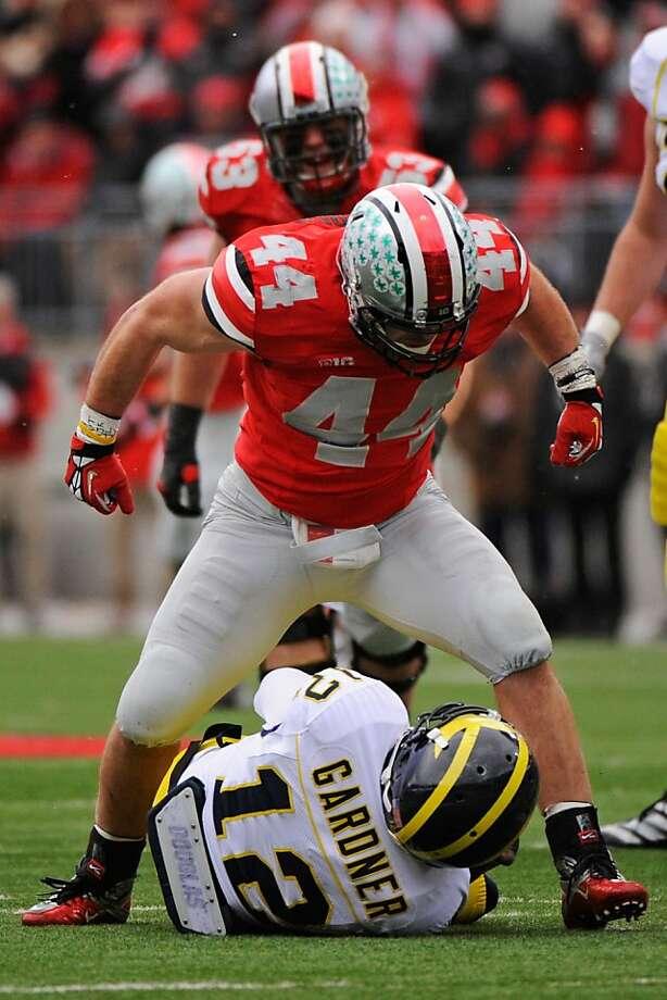 Ohio State's Zach Boren straddles Michigan quarterback Devin Gardner after a first-half sack in Columbus. Photo: Jamie Sabau, Getty Images