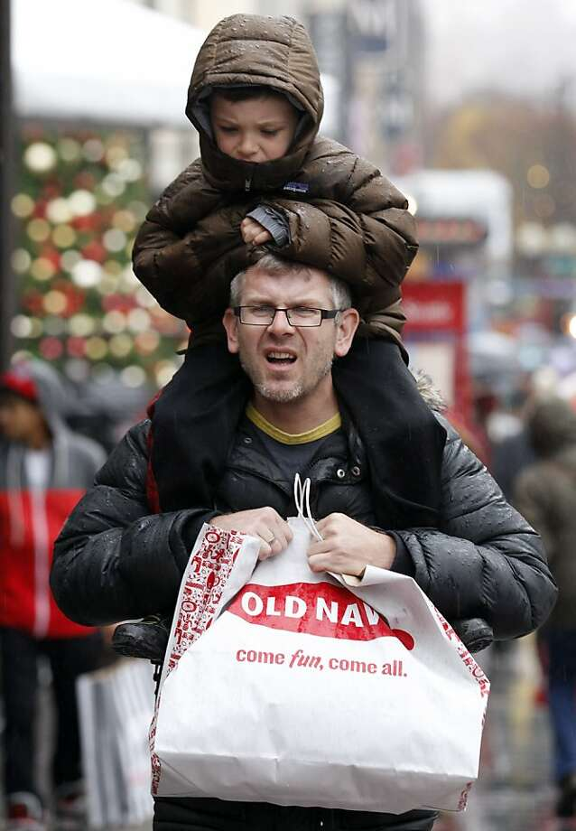 Soren Eberhardt carries his son Johann, 5, on his shoulders as the pair shop Friday, Nov. 23, 2012, in Seattle.  Black Friday, the day when retailers traditionally turn a profit for the year, got a jump start this year as many stores opened just as families were finishing up Thanksgiving dinner. (AP Photo/Elaine Thompson) Photo: Elaine Thompson, Associated Press