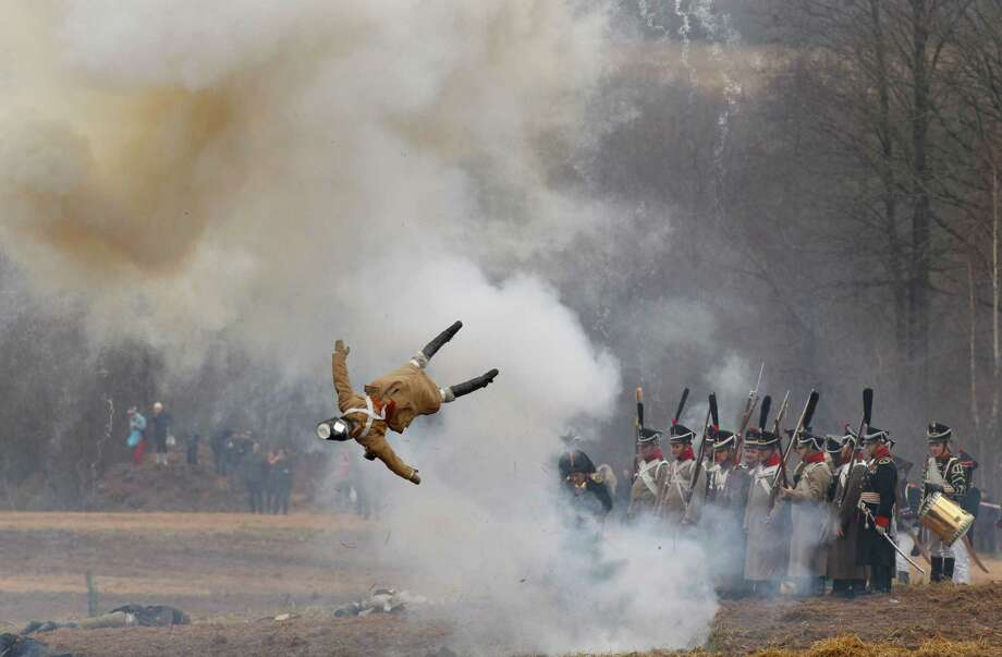 Men dressed as 1812-era Russian and French soldiers re-enact a staged battle as a dummy soldier is blown up, near the Belarus village of Bryli, about 115 kilometers (70 miles) east of the capital, Minsk, Saturday, Nov. 24, 2012, to mark the 200th anniversary of the Berezina battle during Napoleon's army retreat from Russia. Photo: Sergei Grits, Associated Press / AP